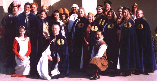 A group of people wearing blue velvet order robes with laurel wreath.